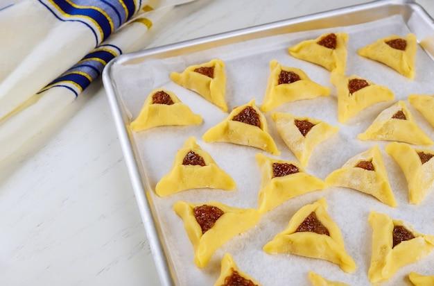Biscuits triangulaires crus sur une plaque de four avec tallit pour la fête juive pourim.