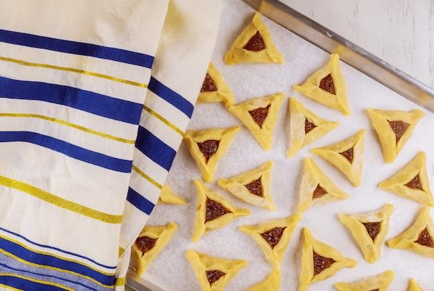 Biscuits triangulaires sur la plaque du four avec du tallit.