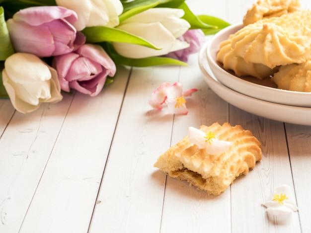Biscuits et tulipes sur une table en bois.