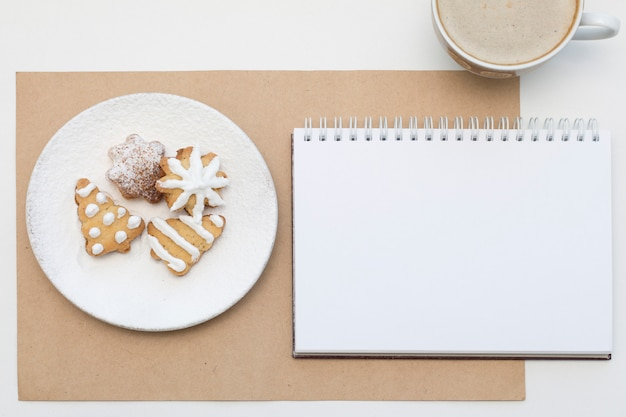Biscuits de vacances et bloc-notes vierge. maquette de noël de café. vue de dessus.