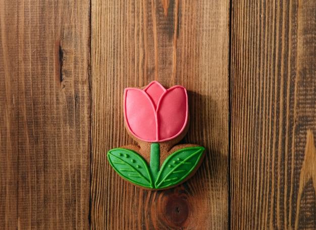 Biscuits de vacances glaçage fleur tulipe rouge fond en bois