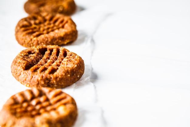 Biscuits végétaliens aux amandes de patate douce ou de citrouille sur fond blanc, gros plan.