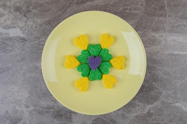 Biscuits verts et jaunes, sur l'assiette, sur la surface en marbre