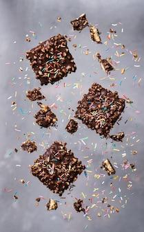 Biscuits volants. pépites de chocolat avec des noix et des points saupoudrés de sucre tombant en mouvement.