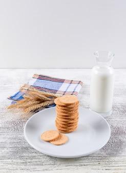 Biscuits vue latérale avec du lait sur une table en bois blanc et fond blanc vertical 2