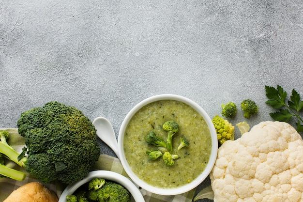 Bisque de brocoli et de chou-fleur à plat dans un bol avec espace pour copie