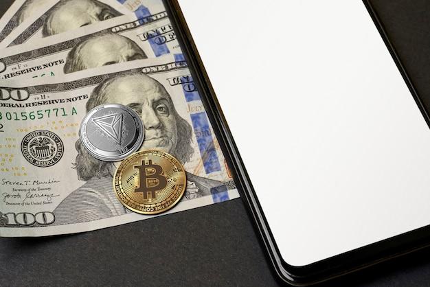 Bitcoin allongé sur des billets de cent dollars et un smartphone