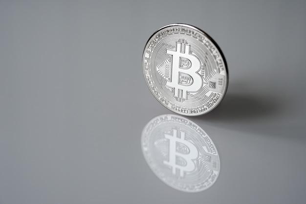 Bitcoin d'argent (btc) isolé sur une surface réfléchissante