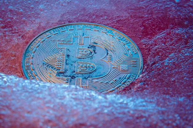 Bitcoin d'argent, monnaie numérique en ligne de pièce de monnaie bit gelée dans la glace bleue