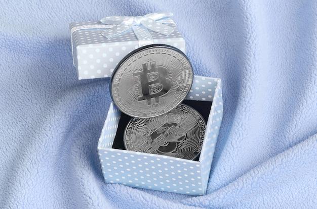 Le bitcoin d'argent se trouve dans une petite boîte-cadeau bleue avec un petit noeud