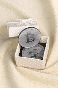Le bitcoin d'argent se trouve dans une petite boîte cadeau orange avec un petit noeud