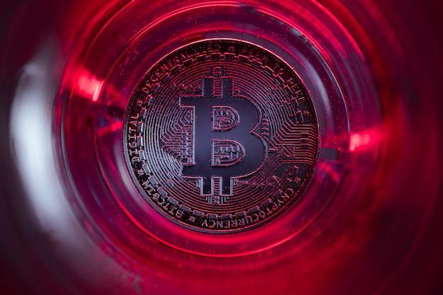 Bitcoin au fond du verre avec de l'eau et des lumières rouges. photo en gros plan.