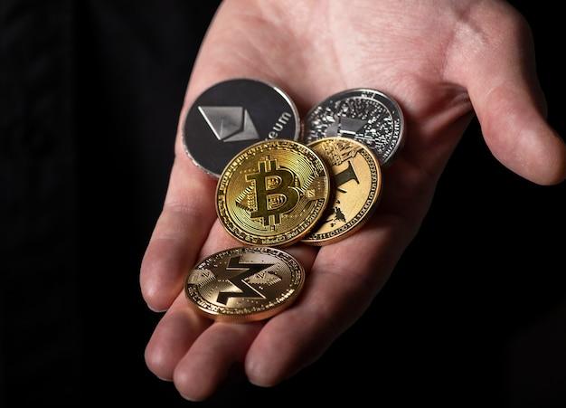 Bitcoin et autres pièces de monnaie crypto différentes dans la paume de la main masculine sur fond noir, gros plan.