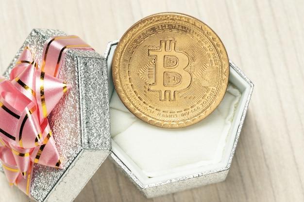 Bitcoin et boîte-cadeau de pièce virtuelle d'or avec ruban rose