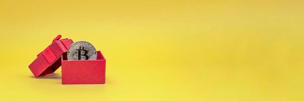 Bitcoin en cadeau. cadeau d'investissement pièce de bitcoin dans une boîte-cadeau sur fond jaune. carte postale pour l'impression, bannière avec place pour le texte.