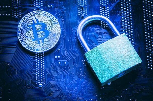 Bitcoin avec cadenas sur la carte mère de l'ordinateur.