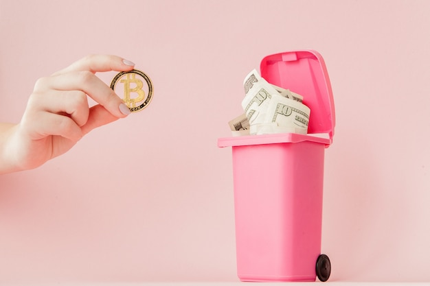 Bitcoin dans la main d'une femme et dollars dans une poubelle
