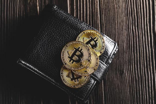 Bitcoin avec dollar sur sac à main isolé noir