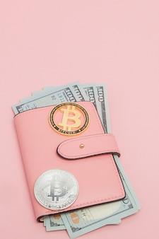 Bitcoin et dollars dans un portefeuille rose sur le rose
