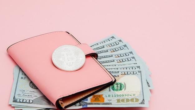 Bitcoin, dollars et portefeuille rose sur fond rose avec espace de copie.