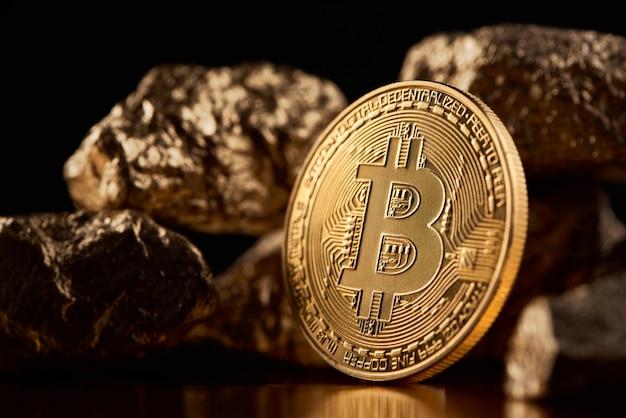 Bitcoin doré à côté de morceaux d'or