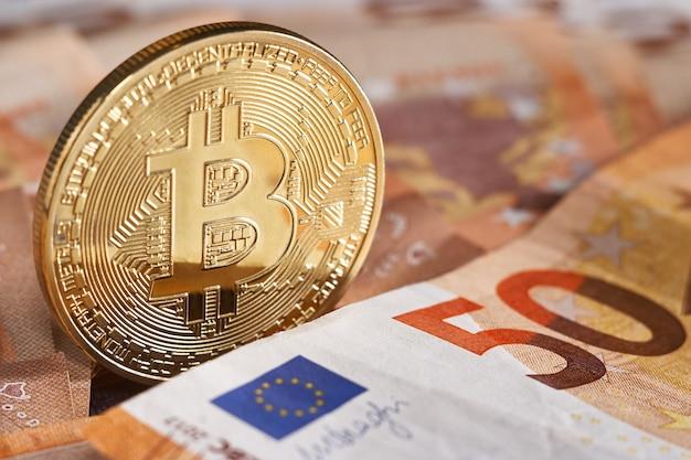 Bitcoin doré sur fond de cinquante billets en euros. bitcoin crypto monnaie, technologie blockchain, argent numérique, concept minier, bitcoin sur facture de 50 euros.
