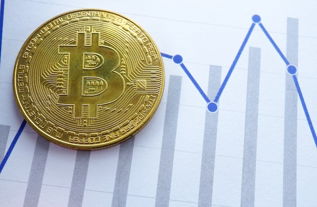 Un bitcoin doré sur fond de graphique. compte de technologie électronique des finances.