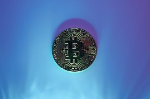 Un bitcoin doré isolé sur fond bleu close-up with copy space
