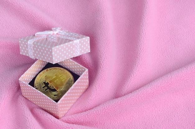 Le bitcoin doré se trouve dans une petite boîte cadeau rose avec un petit noeud