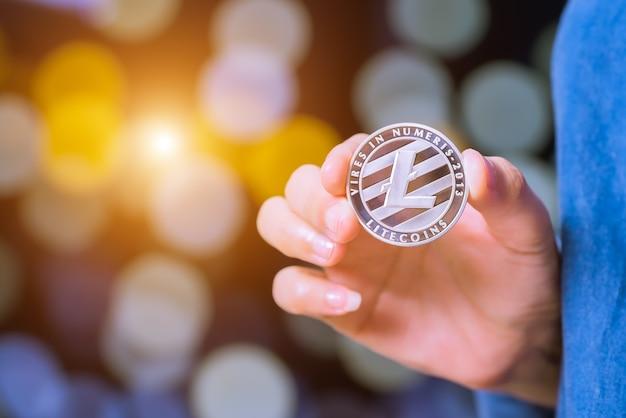 Bitcoin, ethereum, litecoin, ondulation. les femmes tiennent la monnaie de crypto-monnaie en main