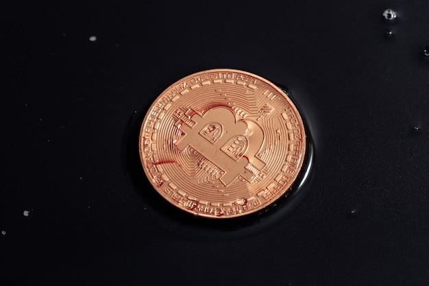 Bitcoin sur fond noir. la crise économique mondiale. le bitcoin n'est pas une monnaie stable. photo macro