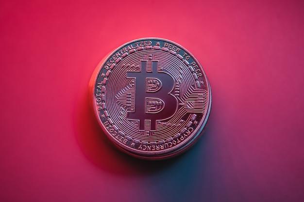 Bitcoin sur fond rétroéclairé violet. monnaie en ligne. photo en gros plan
