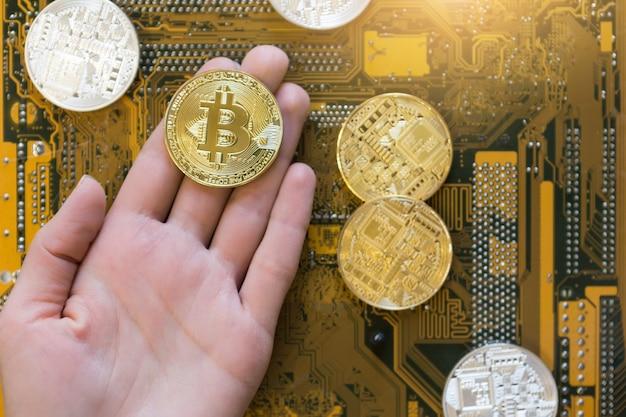 Bitcoin et monnaie crypto virtuelle mondiale sur la carte mère de l'ordinateur en arrière-plan, vue de dessus à plat.