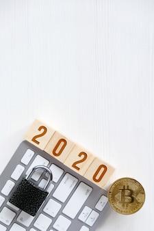 Bitcoin avec des nombres sur des cubes sur un clavier en bois blanc fond un verrou.