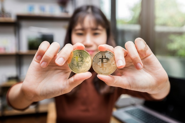 Bitcoin d'or (crypto-monnaie) dans la main de femme d'affaires
