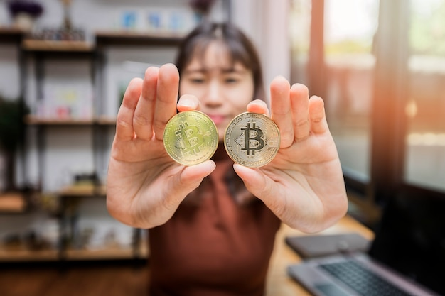 Bitcoin d'or (crypto-monnaie) dans les mains de la femme d'affaires.