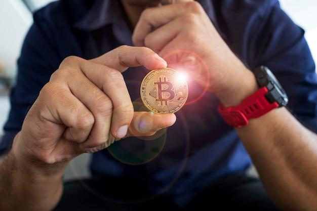 Bitcoin d'or dans une main d'homme d'affaires au bureau