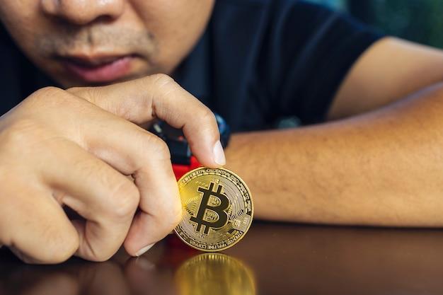Bitcoin d'or dans une main d'homme d'affaires sur la table