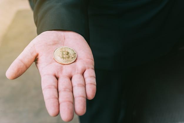 Bitcoin d'or dans une main d'homme, symbole digitall d'une nouvelle monnaie virtuelle.