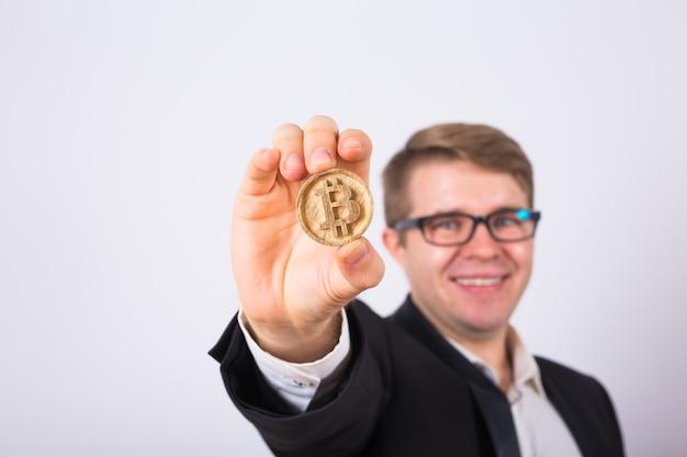 Bitcoin d'or dans une main d'homme, symbole numérique d'une crypto-monnaie virtuelle.