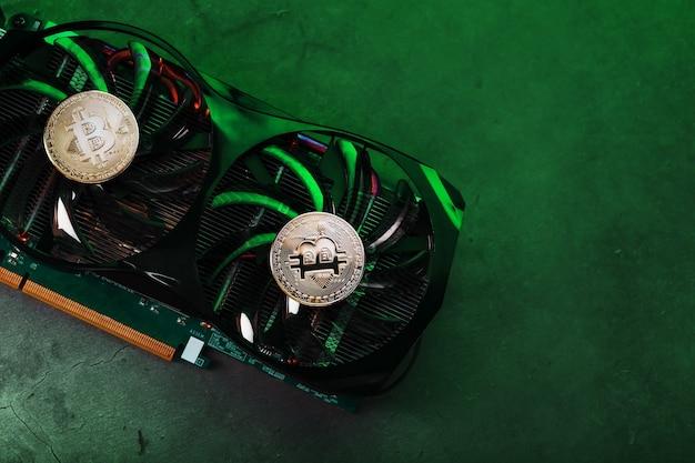 Bitcoin d'or sur le refroidisseur de carte vidéo avec éclairage au néon vert dans le style cyberpunk. le concept d'extraction et d'extraction de crypto-monnaies, le dispositif d'une ferme de crypto-monnaie.