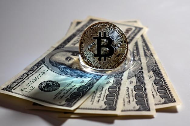Bitcoin d'or sur un stand se dresse sur des billets d'un dollar sur fond blanc