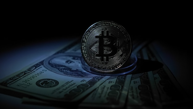 Le bitcoin d'or sur un stand se dresse sur des billets d'un dollar.