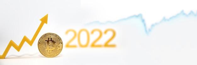 Bitcoin. prix du bitcoin en 2022. taux de crypto-monnaie populaire. la pièce bitcoin sur le tableau des prix pointe vers le haut sur un fond blanc. bannière pour la conception ou l'insertion de texte.