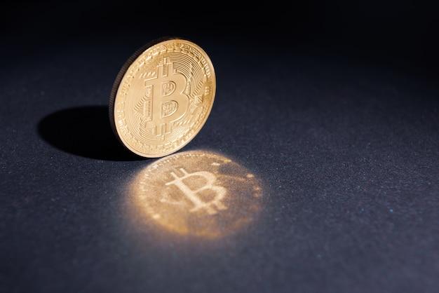 Un bitcoin avec réflexion sur fond sombre.