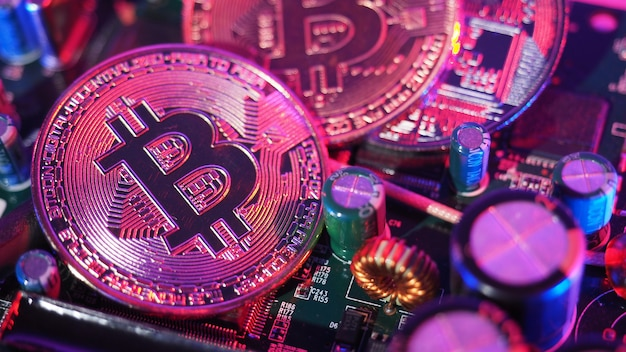 Bitcoin et semi-conducteur. représenter l'exploitation minière dans la crypto-monnaie cause le réchauffement climatique. bitcoins sur carte cpu. gros plan bitcoin avec lumière bleue et rose. circuit imprimé avec pièce de monnaie. concept d'actif en ligne.
