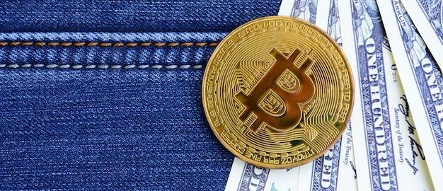 Les bitcoins et les billets d'un dollar doré reposent sur un tissu de jeans.