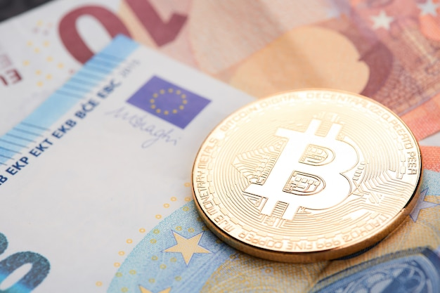 Bitcoins dorés empilés sur fond de billets en euros.