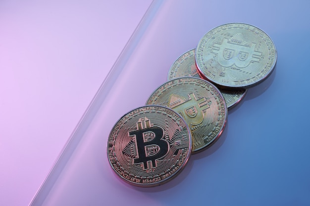 Bitcoins dorés isolés sur fond violet rose bleu néon close-up avec espace de copie, concept de croissance et chute de la crypto-monnaie