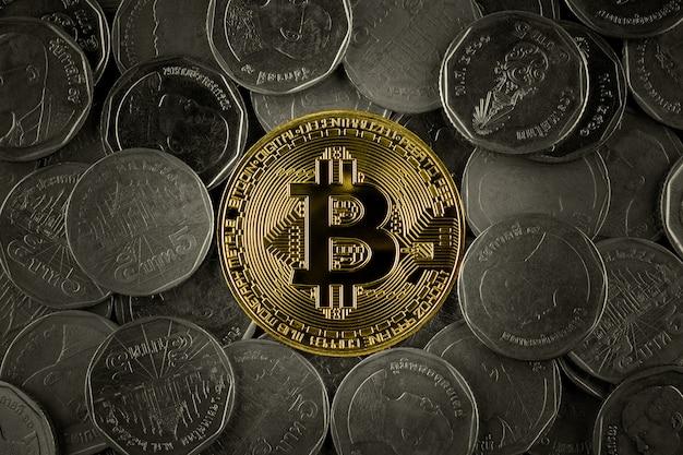 Des bitcoins dorés sur une pile de nombreuses pièces.